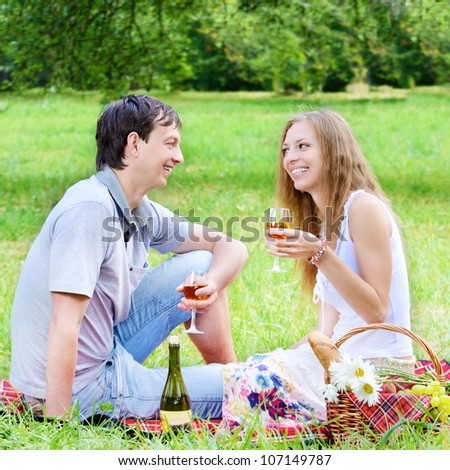 Young happy couple with wineglasses having fun at picnic outdoors