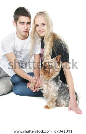 young happy couple with yorkshire terrier over white