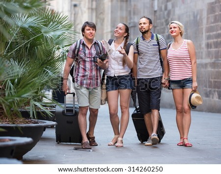 Young happy couples with travel bags walking the city - stock photo