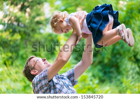Young happy dad playfully tosses his little daughter in the sky - stock photo