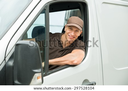 Young Happy Delivery Man Driving Service Delivery Van - stock photo