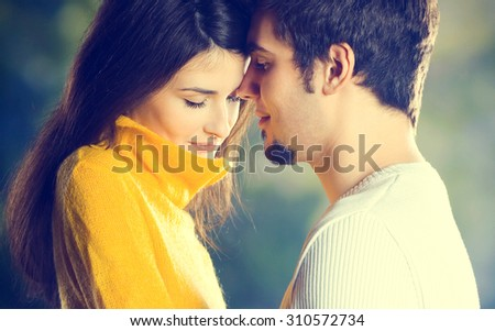 Young happy embracing couple walking together outdoors