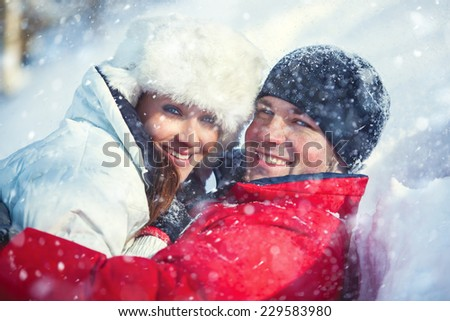 Young happy embracing smiling couple winter outdoors portrait with falling snow. Bright white colors. - stock photo