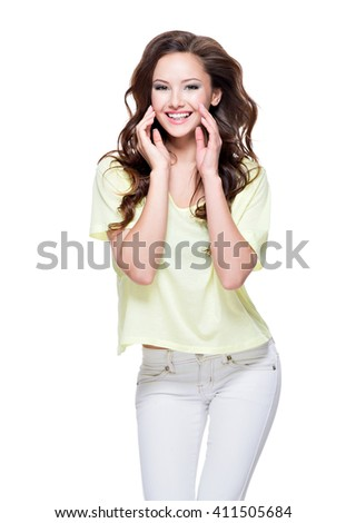 Young happy expressive woman with long brown curly hair posing over white background. Full portrait fashion model at studio. - stock photo