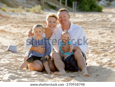 young happy family couple and children sitting on beach sand smiling with blond small baby boy and sweet lovely little girl in summer tourism and holidays concept - stock photo