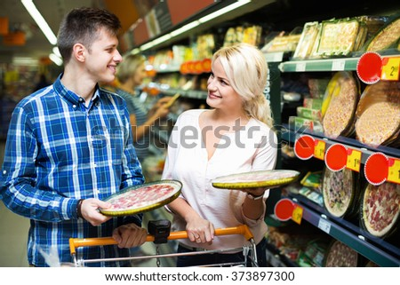 Young happy family couple choosing chilled pizza in food shop - stock photo