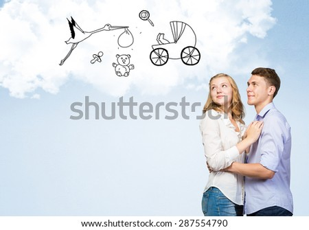 Young happy family couple dreaming of future wealthy life - stock photo