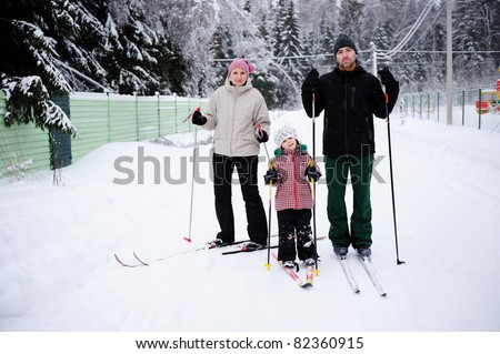 Young happy family enjoy skiing in rural area on winter day