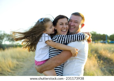 Young happy family frolics outdoors in summer
