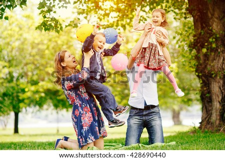 Young happy family having fun in the park - stock photo