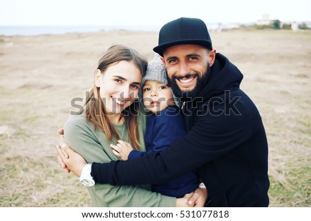 Young happy family having fun together outdoor. Parents enjoying life together. Happiness and harmony. Lifestyle. Photo toned style instagram filters