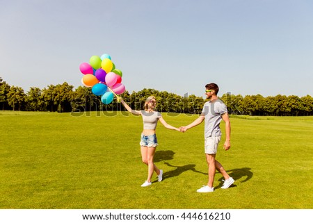 Young happy family having romantic walk with balloons