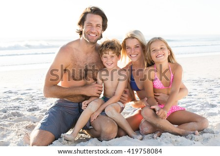 Young happy family in swimsuit at beach looking at camera. Young couple with children at beach in summer holiday. Children playing with sand at beach with their parents. - stock photo