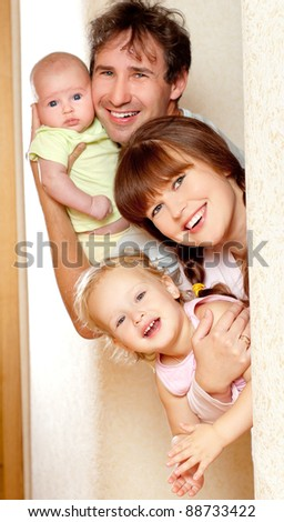 Young, happy family indoors - stock photo