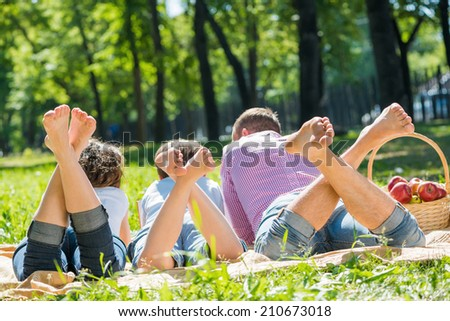 Young happy family lying in park barefoot