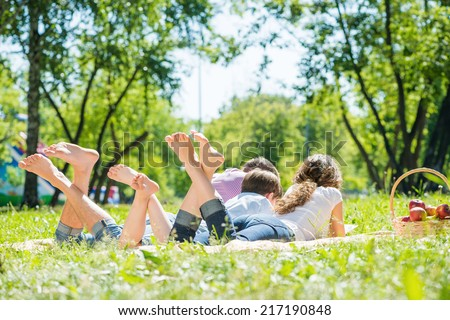 Young happy family lying in park barefoot - stock photo
