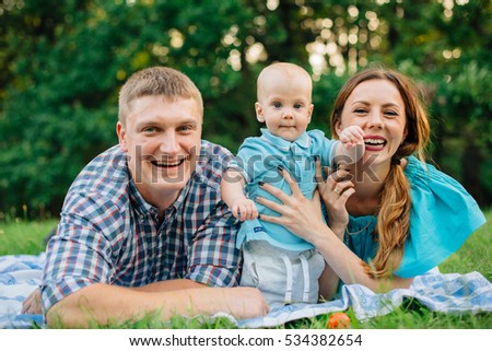 Young happy family lying on blanket and having fun outdoors. Attractive woman in turquoise dress with husband in checkered shirt and cute baby boy son playing in the park. Happy parenting concept.