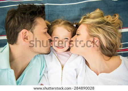 Young happy family lying on the lawn in summer park. - stock photo