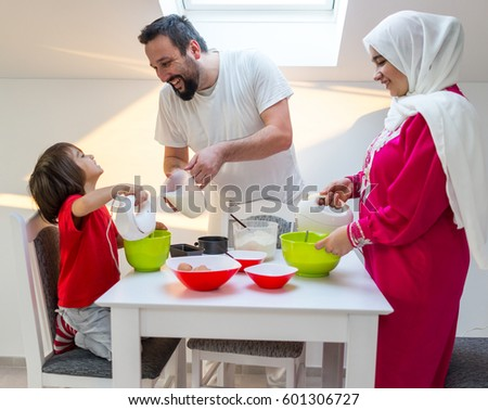 Young happy family making food together