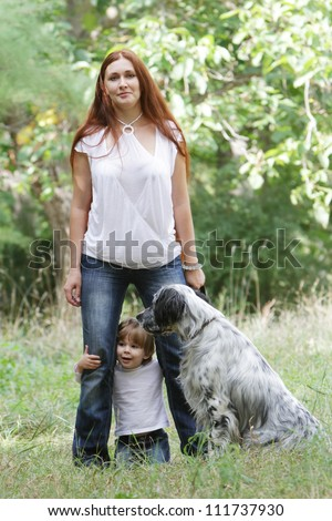 young happy family - mother and child - playing with dog outdoors - stock photo