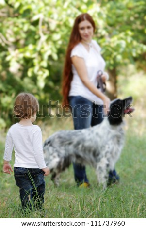 young happy family - mother and child - with dog on natural background