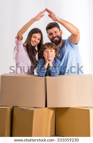 Young happy family moving to a new home, opening boxes - stock photo