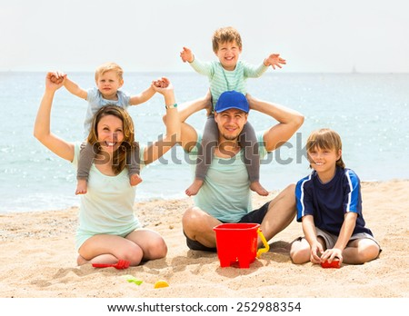 Young happy family of five in the summer on the beach - stock photo