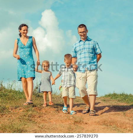 young happy family of four down from the mountains in the background of clouds - stock photo