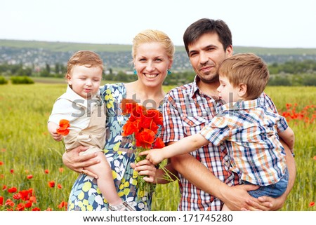 Young happy family of four having fun together outdoor.