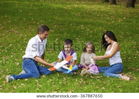 Young happy family of four, resting in the autumn park
