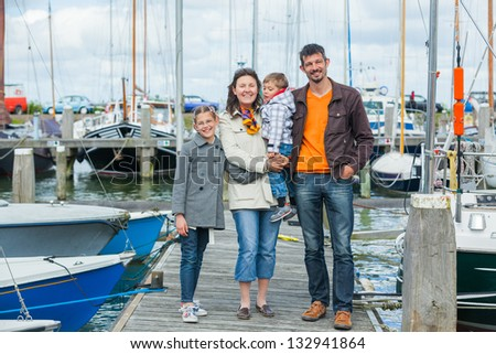 Young happy family of four rests on Yacht Club and is glad at life. - stock photo
