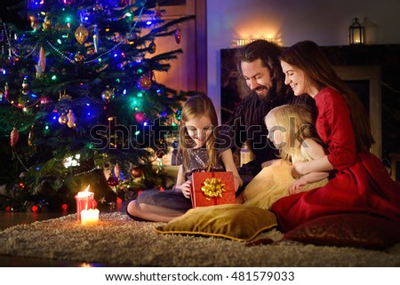 Young happy family of four unwrapping Christmas gifts by a fireplace in a cozy dark living room on Christmas eve