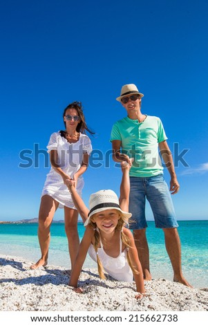 Young happy family of three have fun on tropical vacation - stock photo