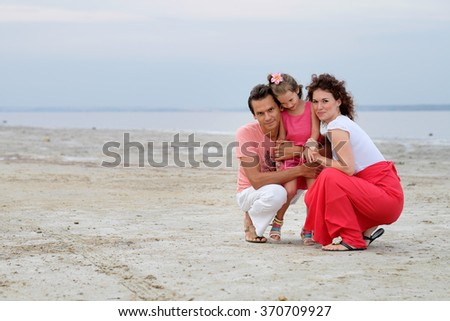 young happy family of three having fun sitting in the sand on beach