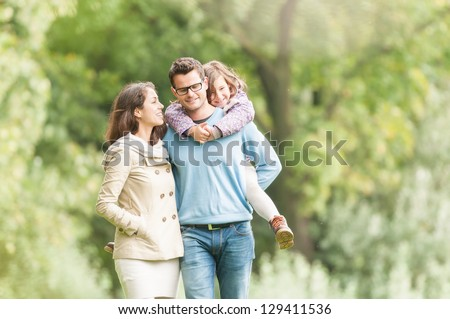 Young happy family of three having fun together outdoor. Pretty little daughter on her father back. Parents and girl look happy and smile. Happiness and harmony in family life. Family fun outside.