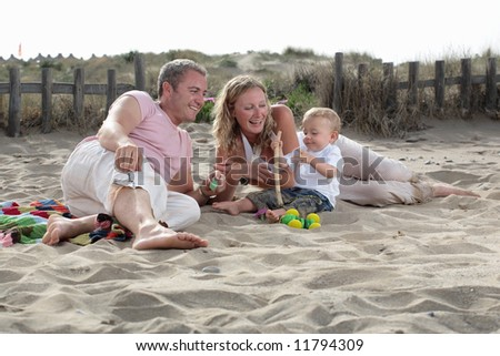young happy family of three on the beach - stock photo
