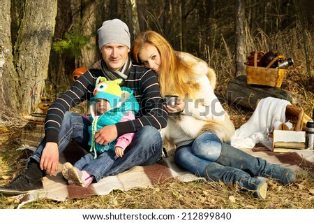 Young happy family on nature in the forest rest - stock photo