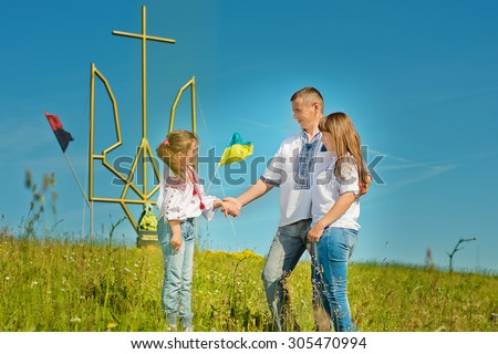 young happy family on the background of the monument to the Ukrainian trident outdoors
