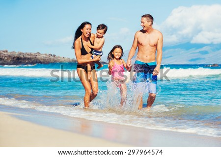 Young Happy Family Playing Having Fun at the Beach Outdoors - stock photo
