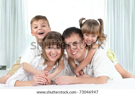 Young happy family playing together on a bed