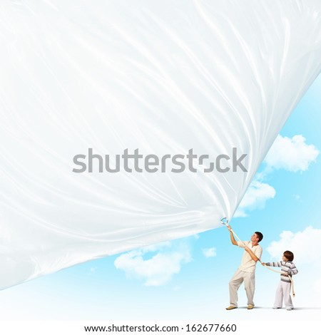 Young happy family pulling blank banner. Place for text - stock photo