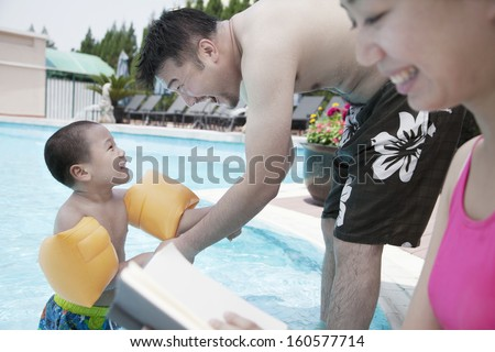 Young happy family relaxing by pool on vacation - stock photo