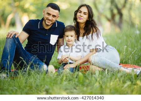 Young happy family spending their time in park  on picnic - stock photo