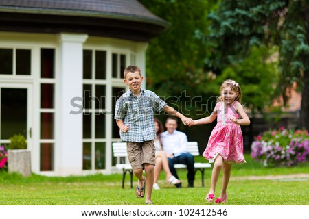 Young happy family - the children are playing and the parents sitting in the sun on a bench in front of their villa