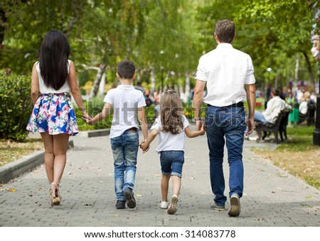 Young happy family walking in autumn park - stock photo
