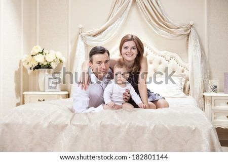 Young happy family with a baby on bed at home  - stock photo