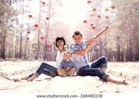 Young happy family with apples outdoors - stock photo
