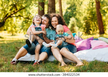 Young happy family with kids having picnic with colored pillows outdoors. Parents with two children relax in a sunny summer garden. Mother, father, little girl and baby boy playing in park. - stock photo