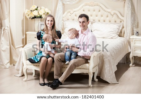 Young happy family with two baby boys at home  - stock photo