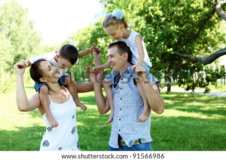 Young happy family with two children in the summer park - stock photo
